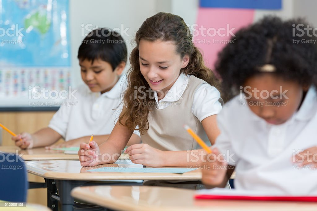 Schoolgirl concentrates while taking test stock photo