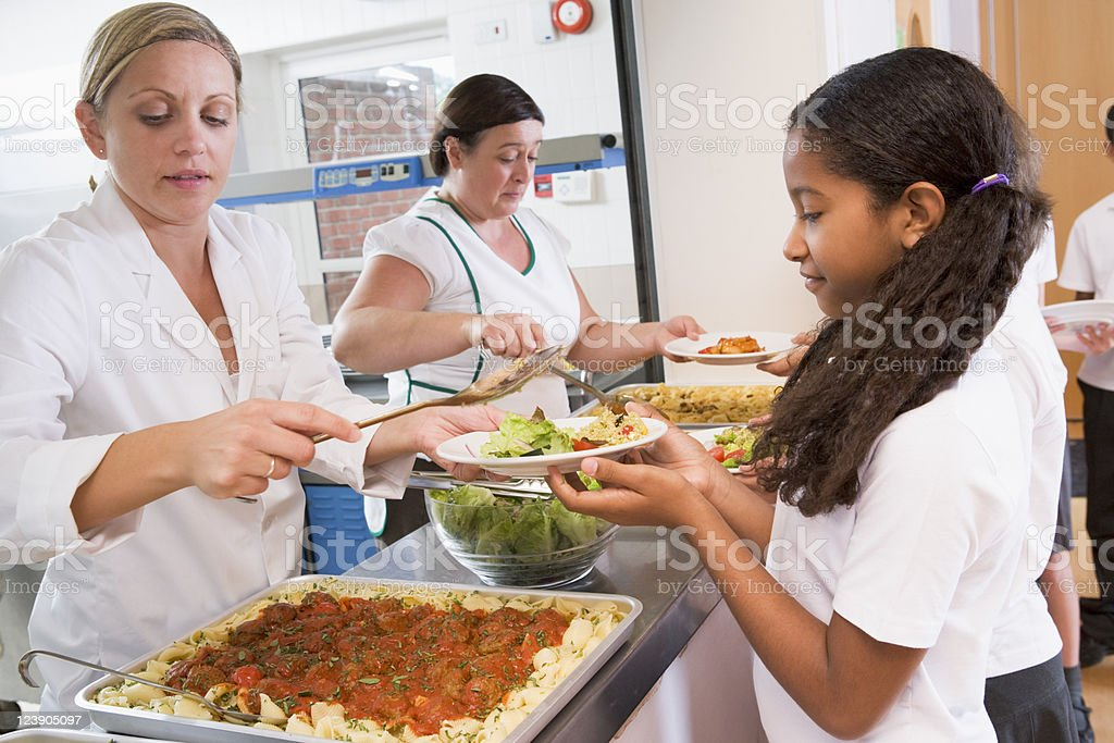 Schoolgirl holding plate of lunch in school cafeteria stock photo