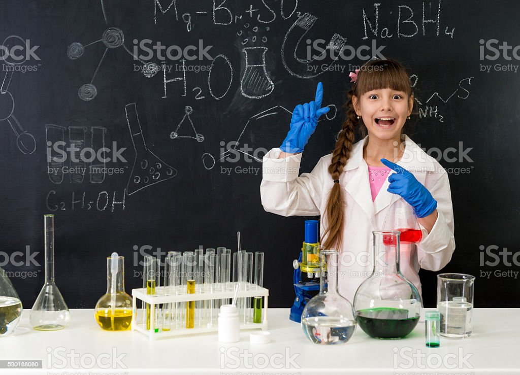 schoolgirl in chemistry lab pointing at formula on blackboard stock photo