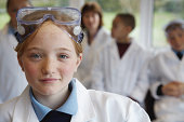 Schoolgirl (11-13) in science class, smiling, portrait (focus on girl)