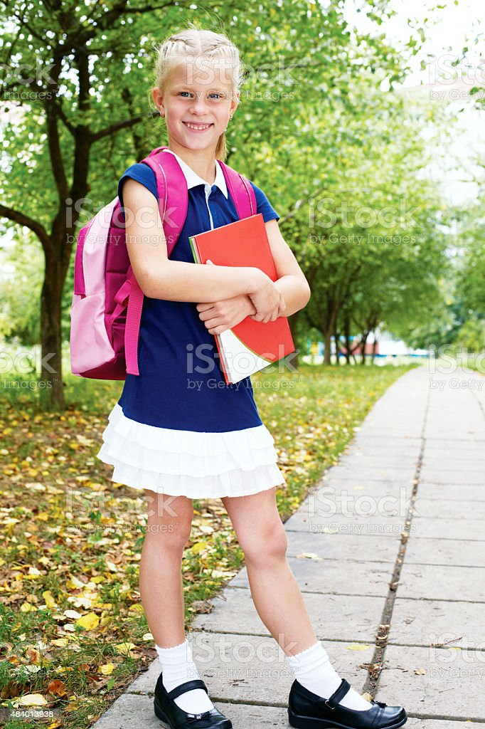 Schoolgirl is on the way to school for the first time. stock photo