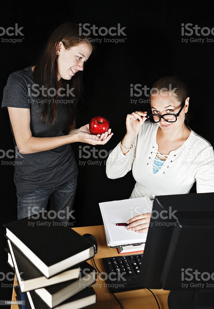 Schoolgirl offers apple to teacher, who smiles over her spectacles royalty-free stock photo