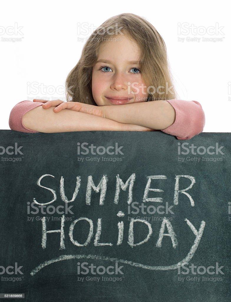 Schoolgirl over blackboard with Summer Holiday text. stock photo