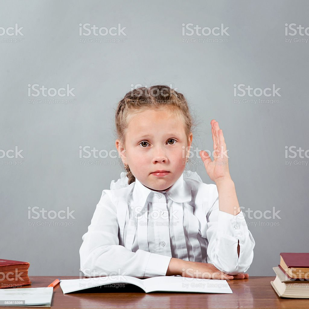 Schoolgirl raising her hand knowing the answer stock photo