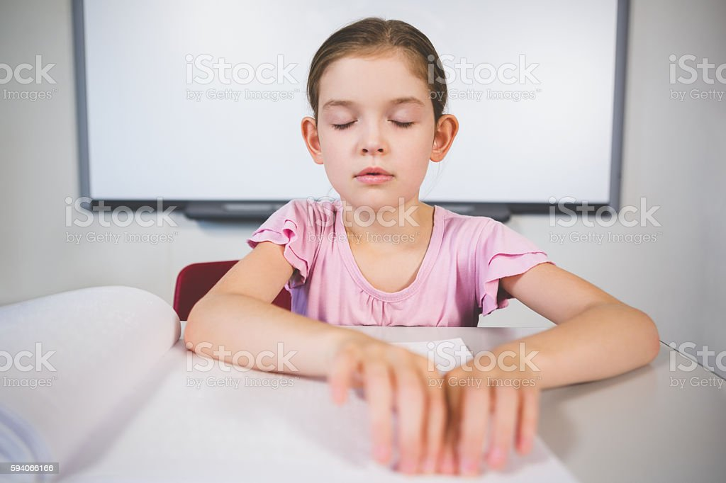 Schoolgirl reading a braille book in classroom stock photo