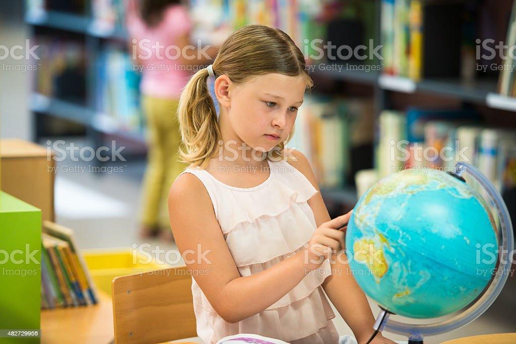 Schoolgirl Reading The World Globe stock photo