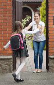 Schoolgirl running to her mother waiting for her after school