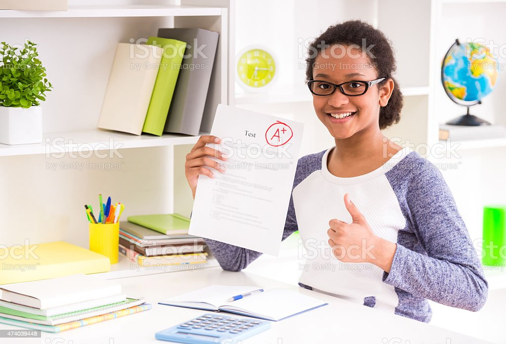 Schoolgirl showing a A+ test result with a smile in her face stock photo