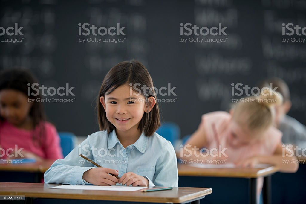 Schoolgirl Sitting at Her Desk stock photo