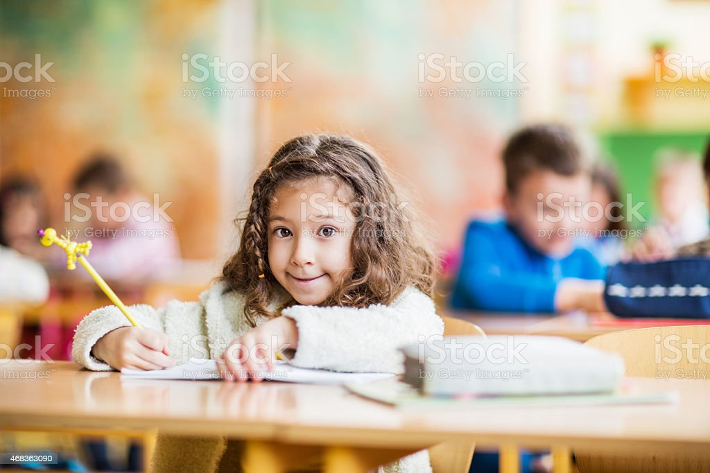 Schoolgirl sitting in the classroom and looking at the camera. stock photo