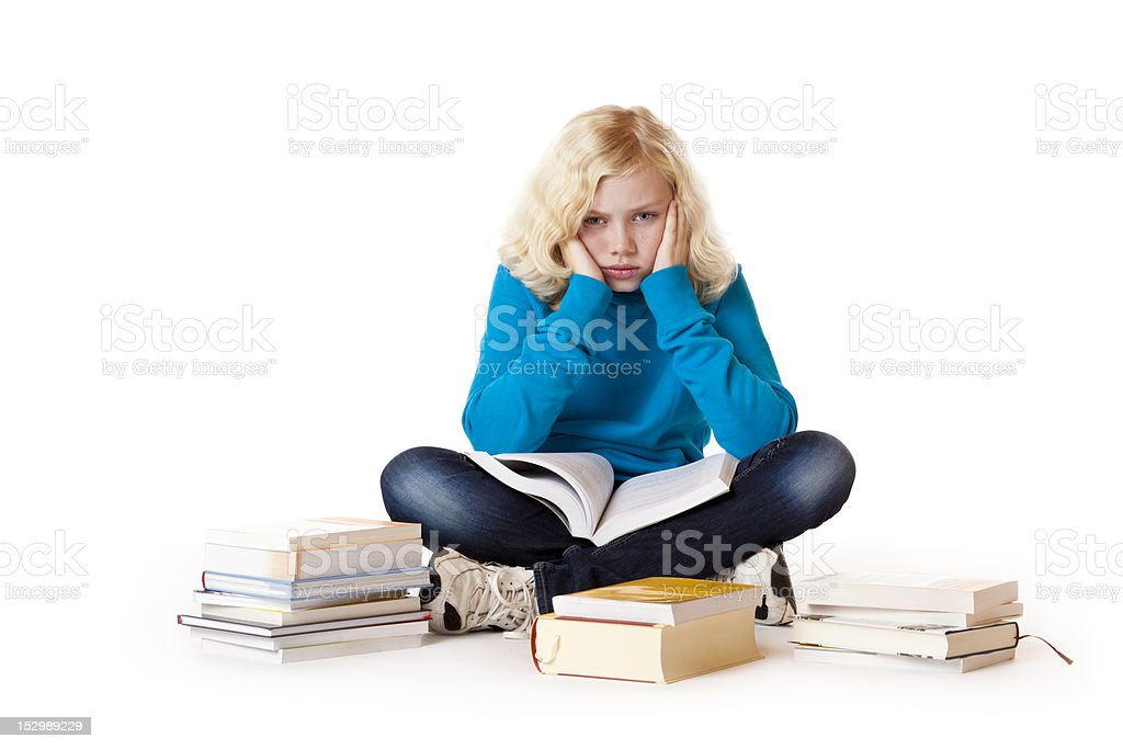 Schoolgirl sitting tired, frustrated on floor learning with study books royalty-free stock photo