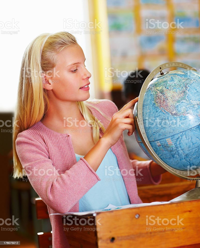 Schoolgirl studying the world globe in classroom royalty-free stock photo