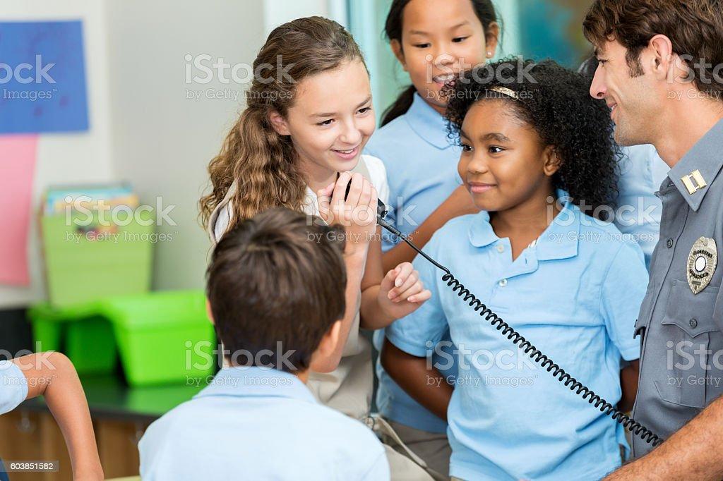 Schoolgirl talks on police officer's walkie talkie stock photo