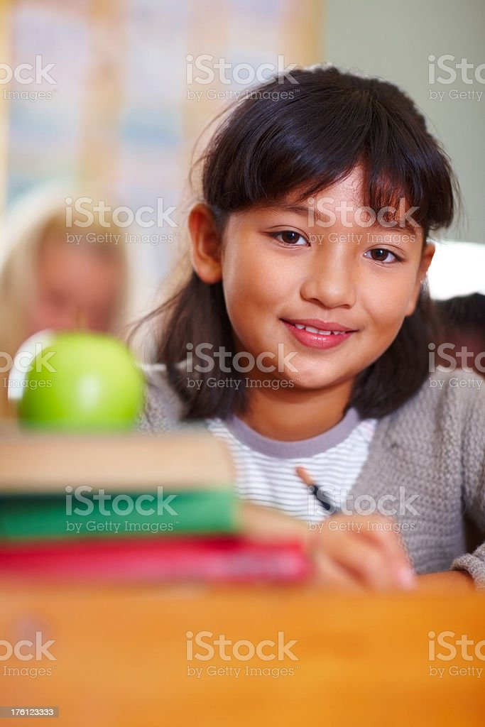Schoolgirl with a green apple kept on her books royalty-free stock photo