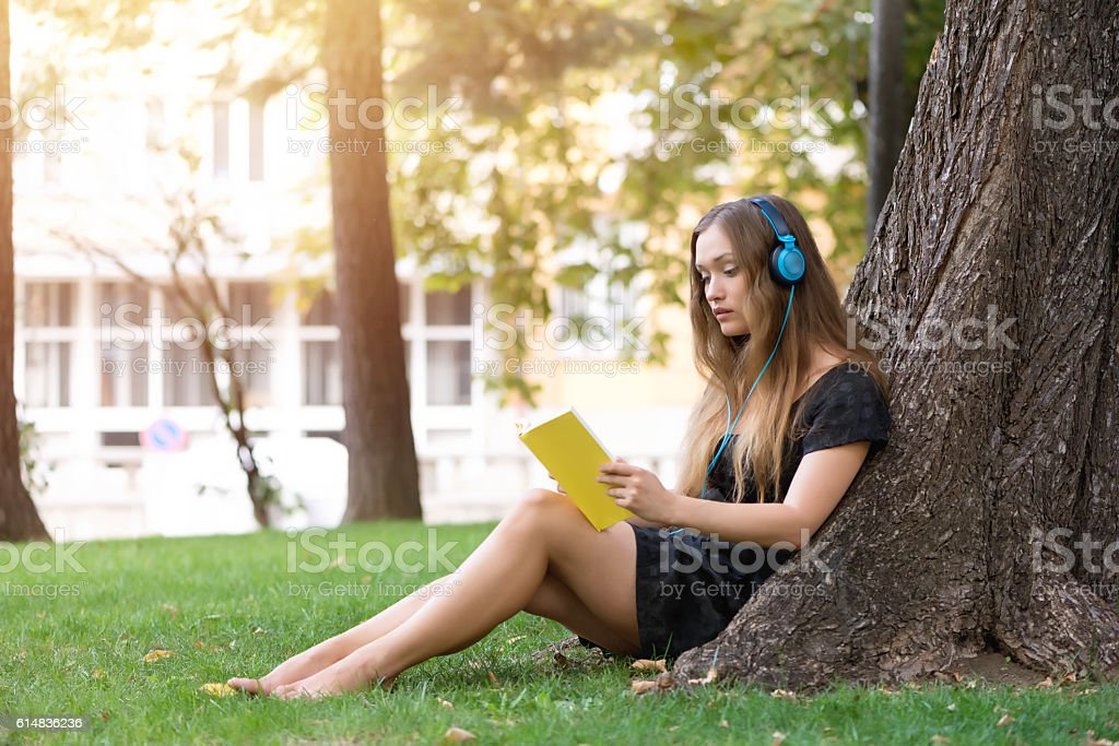 Schoolgirl with headphones and book resting in park stock photo
