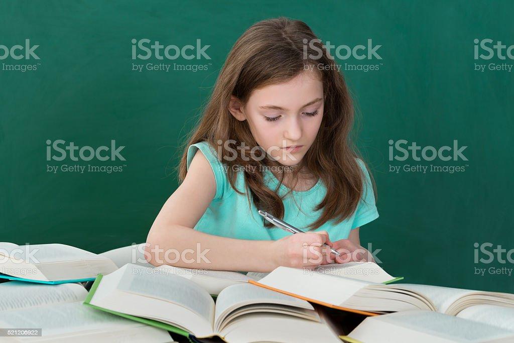Colegiala con libros abierto en montaje tipo aula - foto de stock