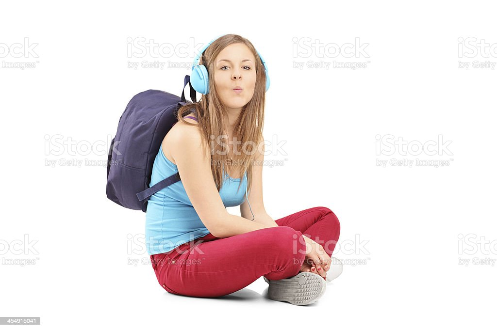 Schoolgirl with speakerphones sitting and giving kisses royalty-free stock photo