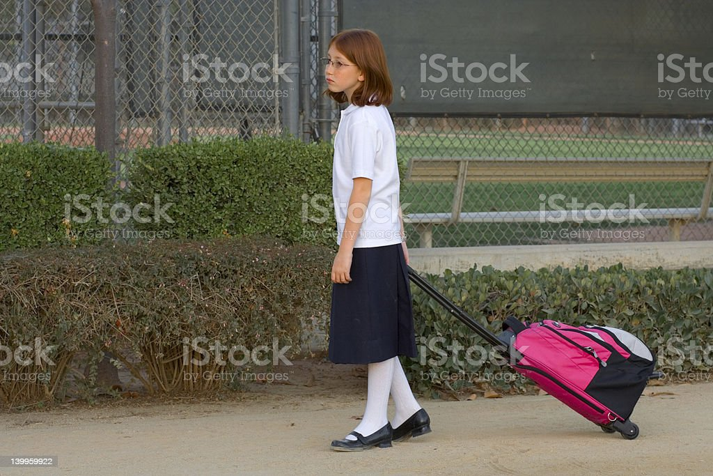 schoolgirl with trolley bag royalty-free stock photo