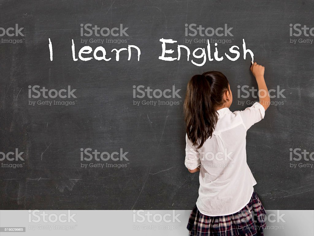 schoolgirl writing I learn English with chalk on blackboard stock photo