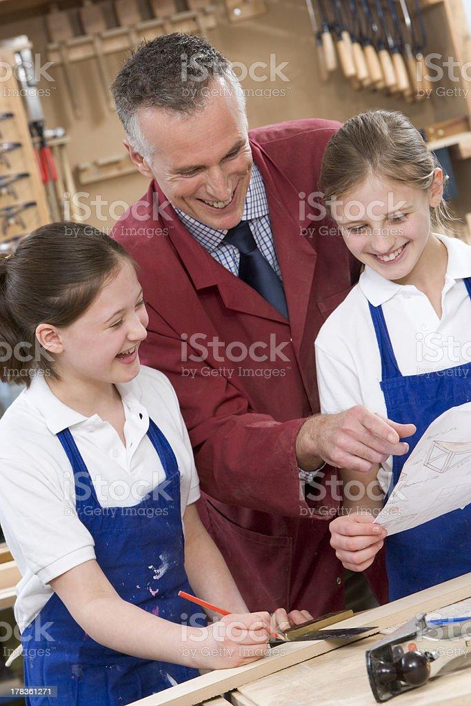 Schoolgirls and teacher in woodwork class stock photo
