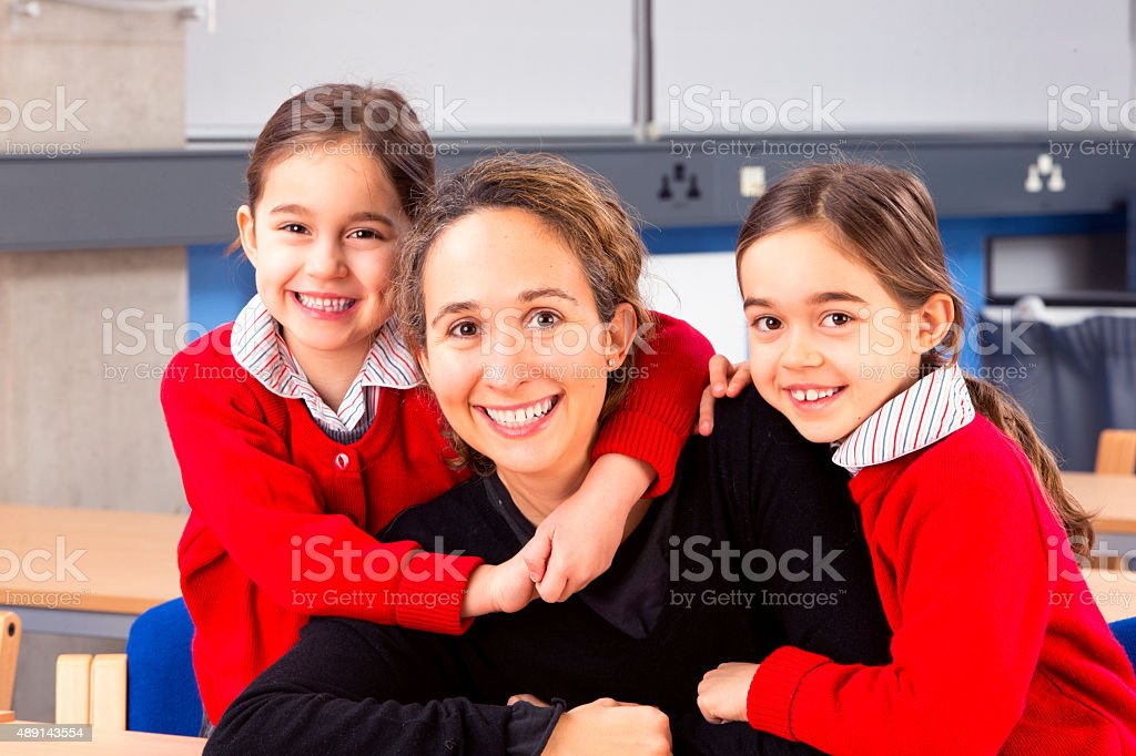 Schoolgirls Embracing Their Mother stock photo