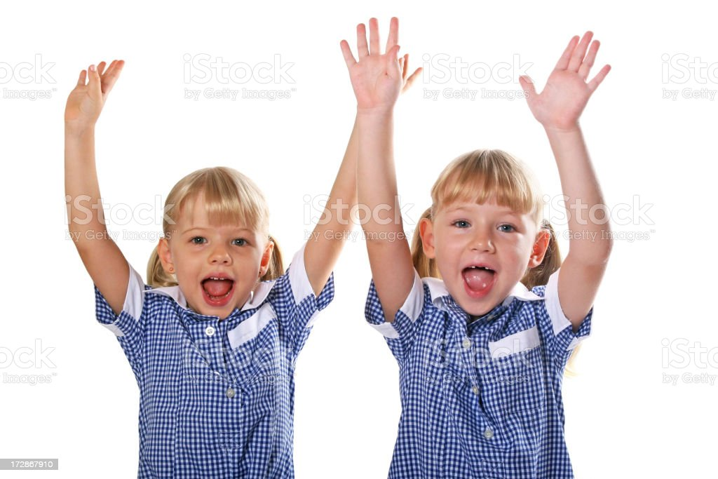 Schoolgirls in uniform with arms raised royalty-free stock photo