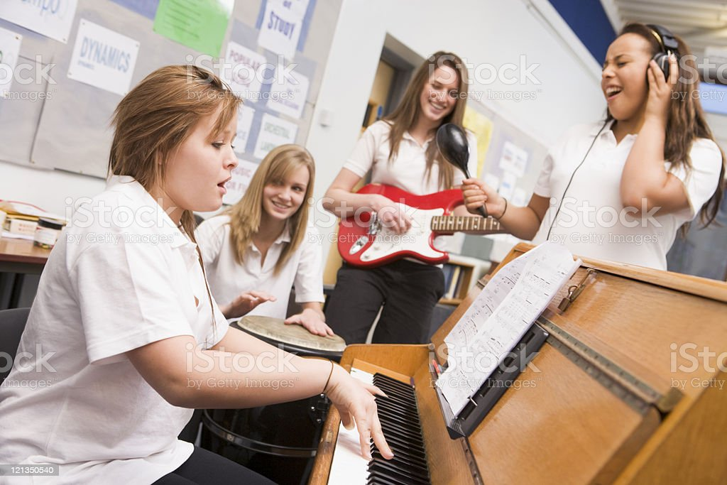 Schoolgirls playing musical instruments in music class stock photo