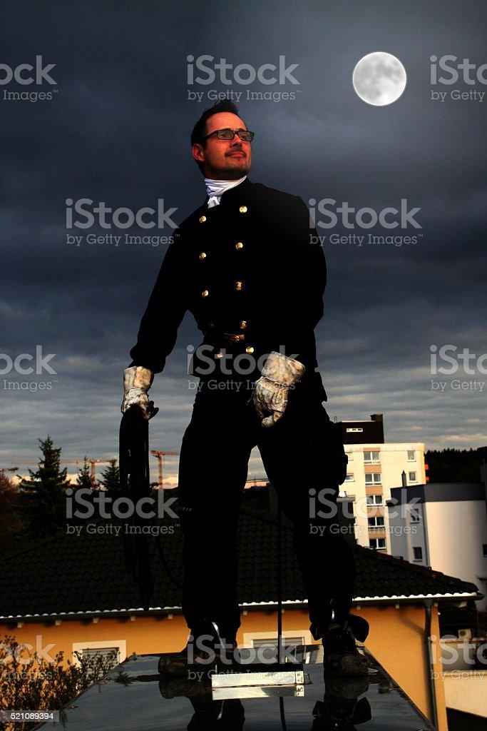 Schornsteinfeger auf dem Dach am Abend stock photo