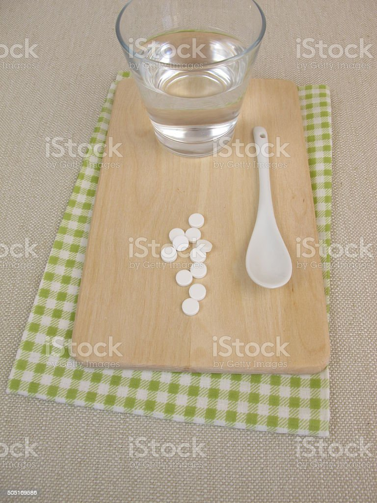 Schuessler salts tablets and glass of water stock photo