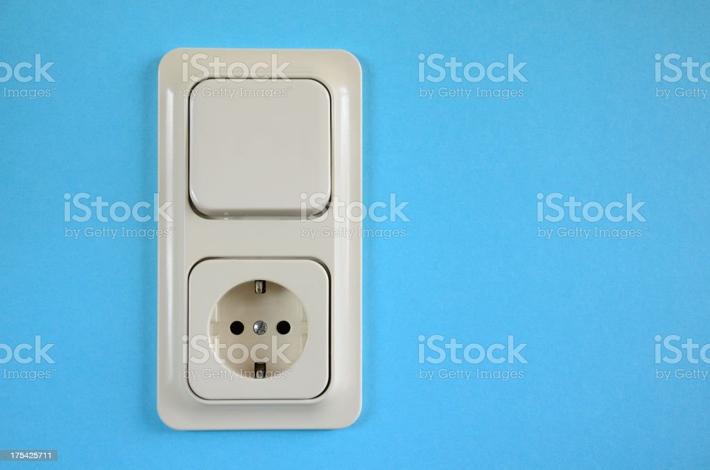 Schuko power socket and light switch on blue wall stock photo