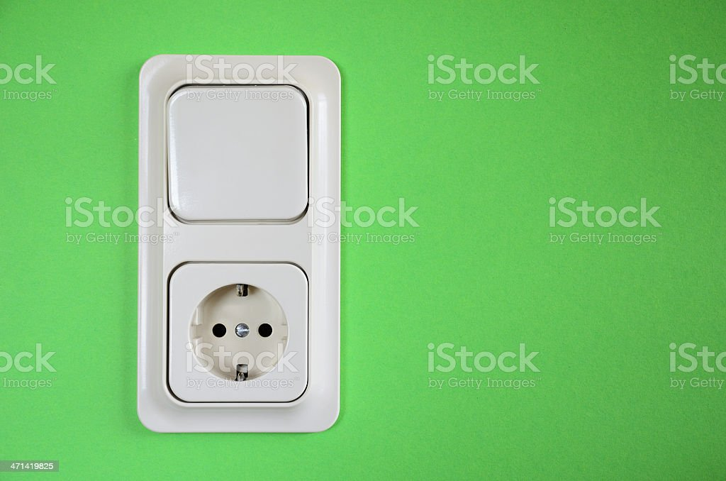 Schuko power socket and light switch on green wall stock photo