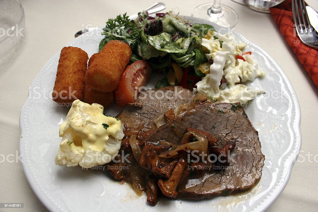 Schweinebraten, Blumenkohl, Kroketten, Tomaten und Salat auf Teller, royalty-free stock photo