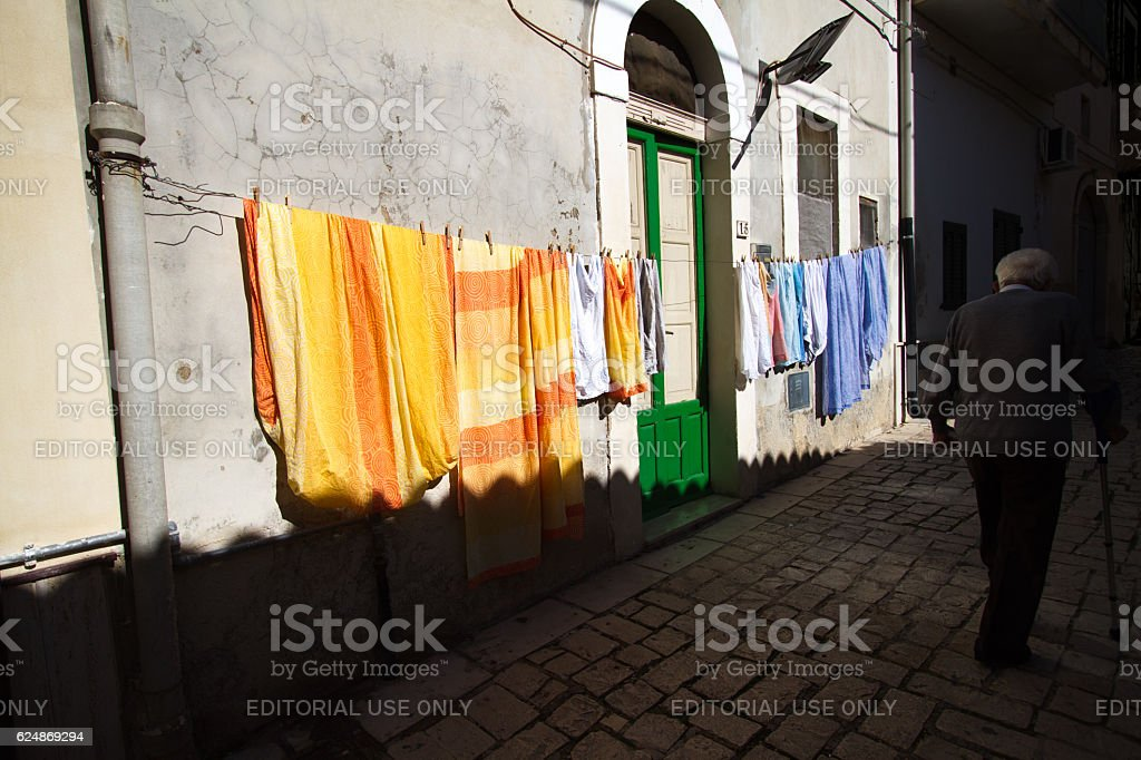Scicli, Sicily: Laundry on Line; Senior with Cane stock photo