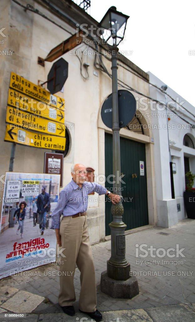 Scicli, Sicily: Senior Man Leans Against Street Lamp stock photo
