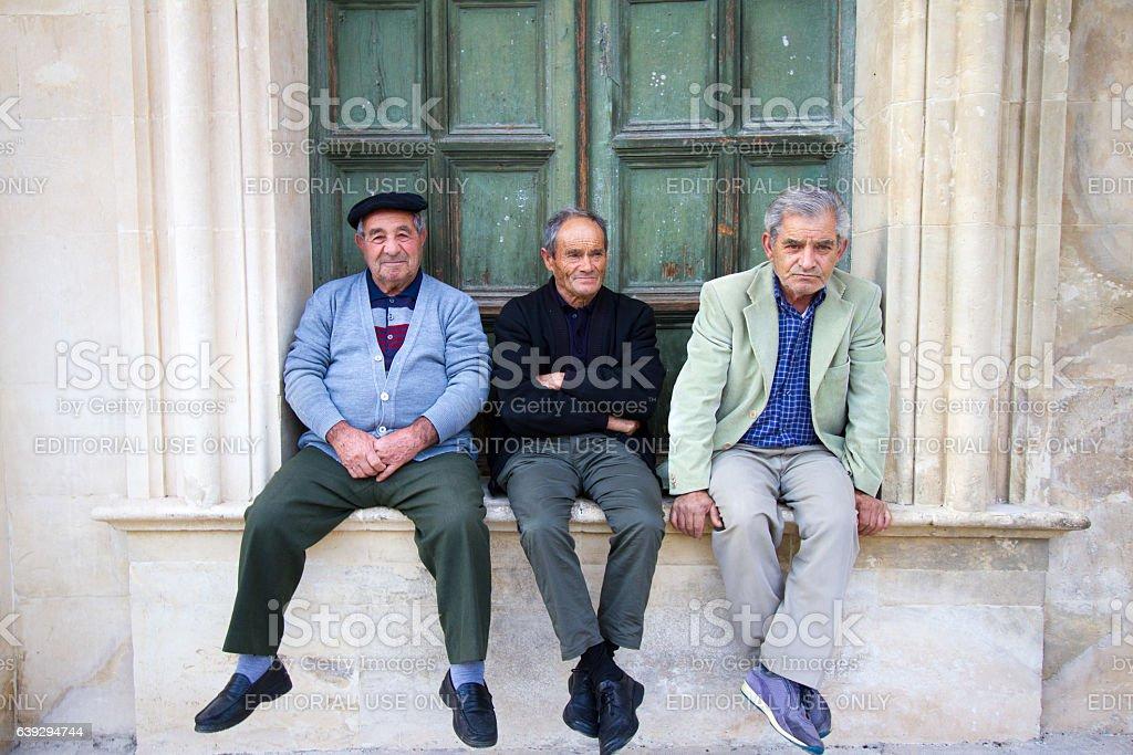 Scicli, Sicily: Three Senior Men Sit on a Window Ledge stock photo