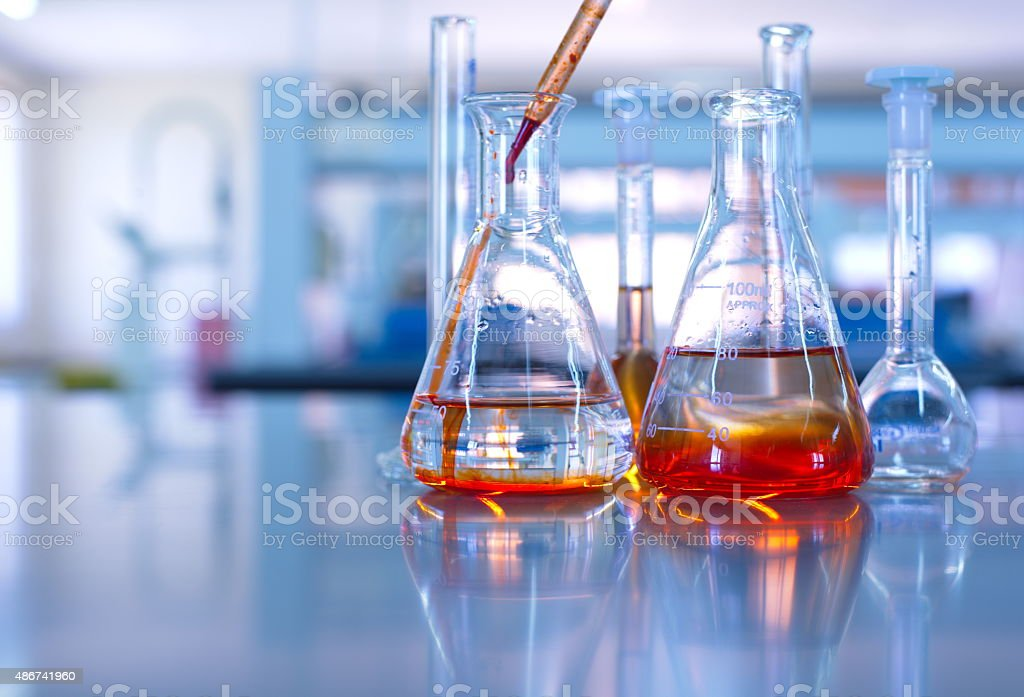 science laboratory glassware orange solution stock photo
