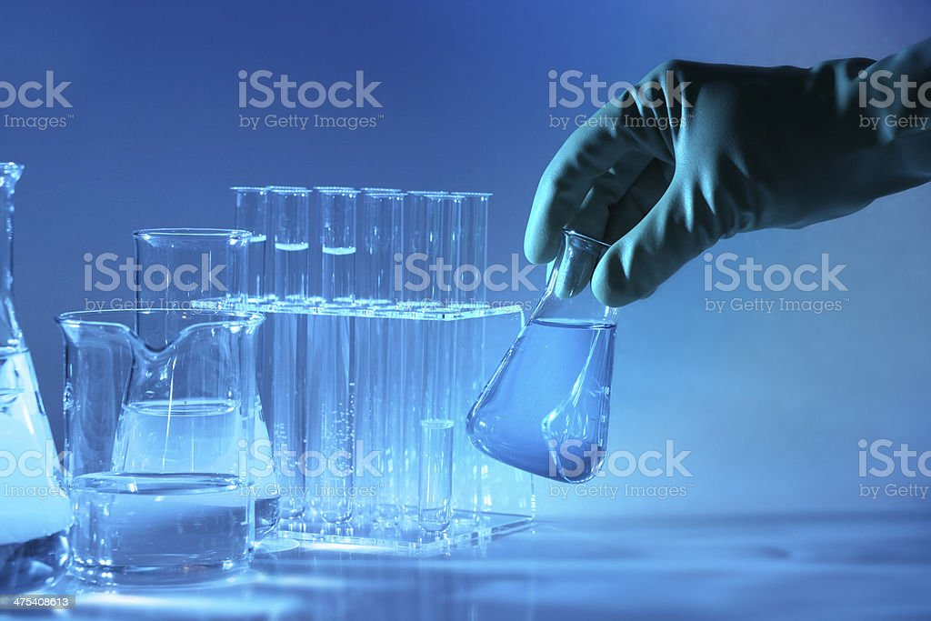 Science laboratory, hand picking glass flask, blue liquid, test tubes stock photo