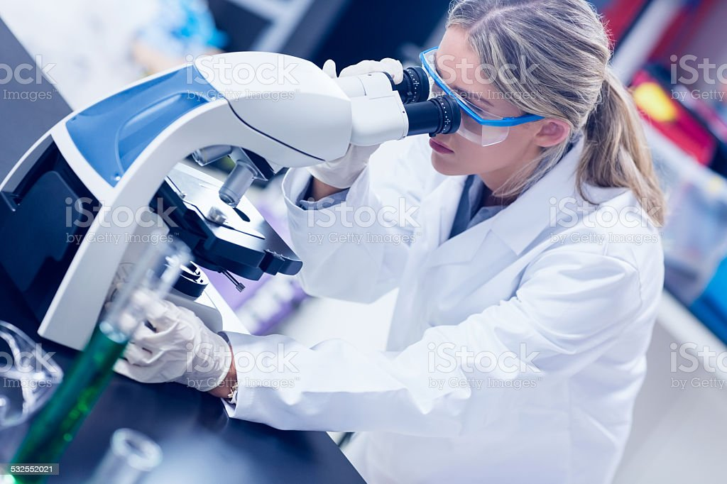 Science student looking through microscope in the lab stock photo