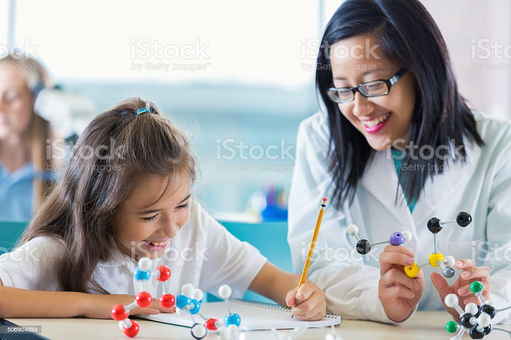 Science teacher helping elementary student study molecule models stock photo
