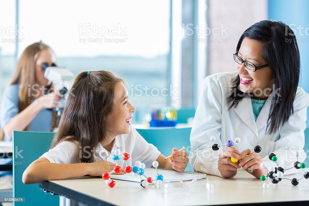 Science teacher helping elementary student with molecule assignment stock photo