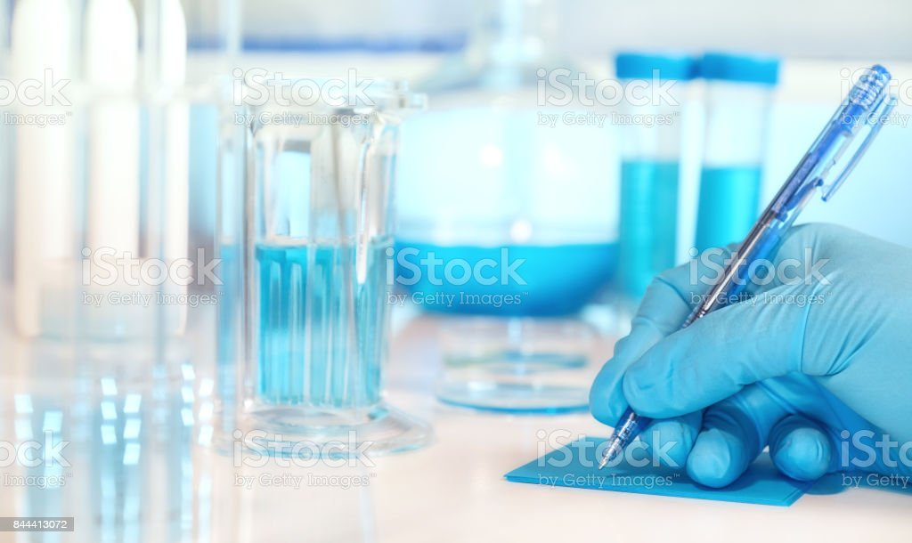 Scientific or medical background with gloved hand holdong microscopic slide glass stock photo