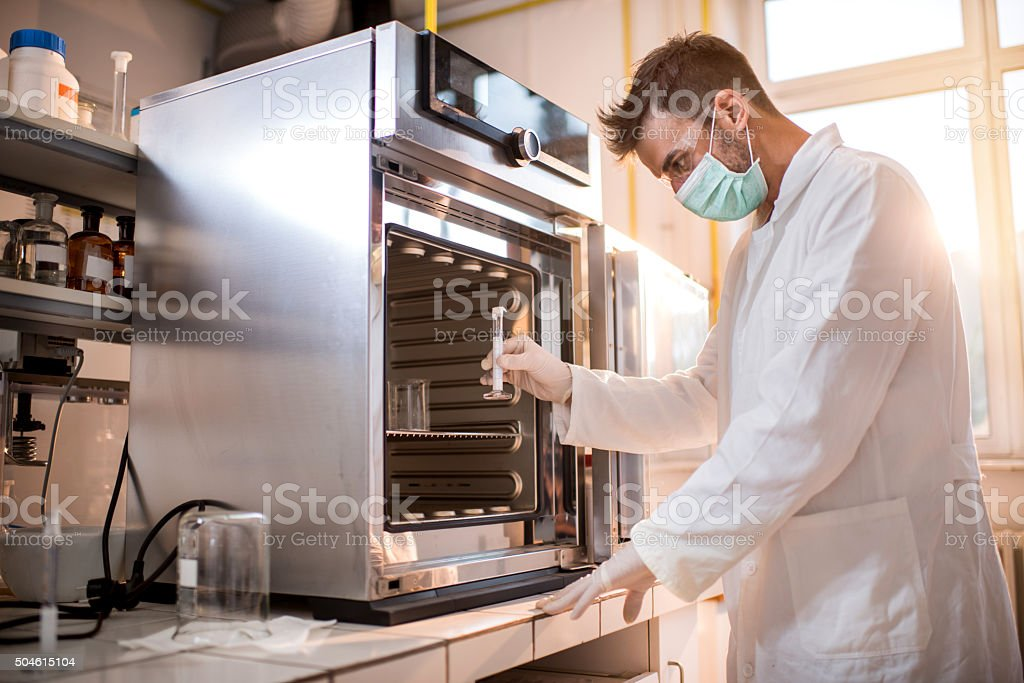 Scientist about to put a test tube into sterilizer. stock photo