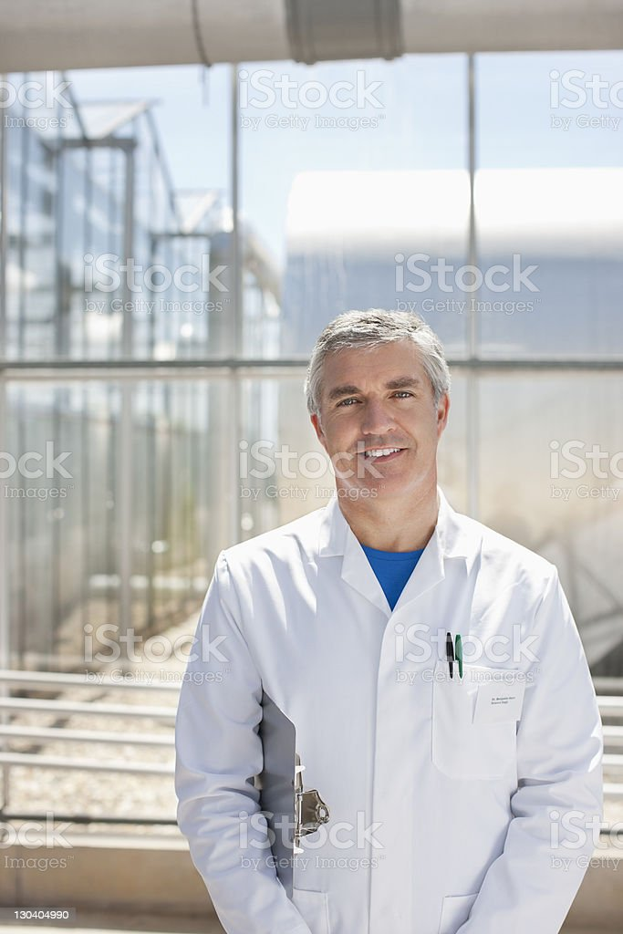 Scientist carrying clipboard in lab stock photo