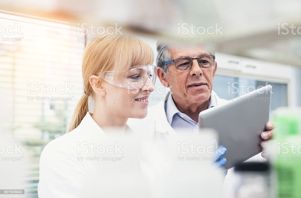 Scientist Discussing Using Digital Tablet stock photo