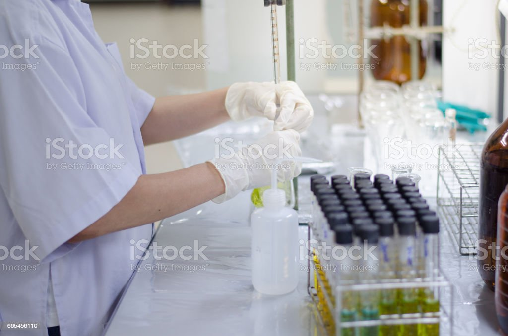 Scientist hand titration at laboratory, stock photo