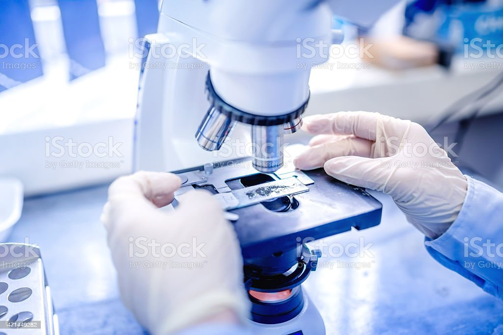 scientist hands with microscope, examining samples and liquid stock photo
