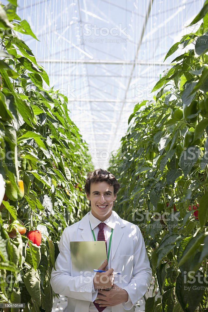 Scientist holding clipboard in greenhouse royalty-free stock photo