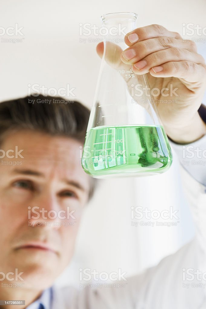 scientist holding up jar of chemicals royalty-free stock photo