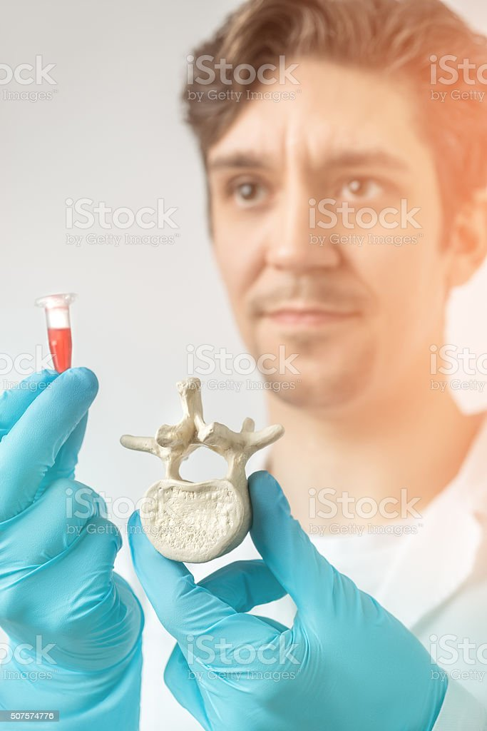 Scientist holds vertebra and a tube with red liquid stock photo