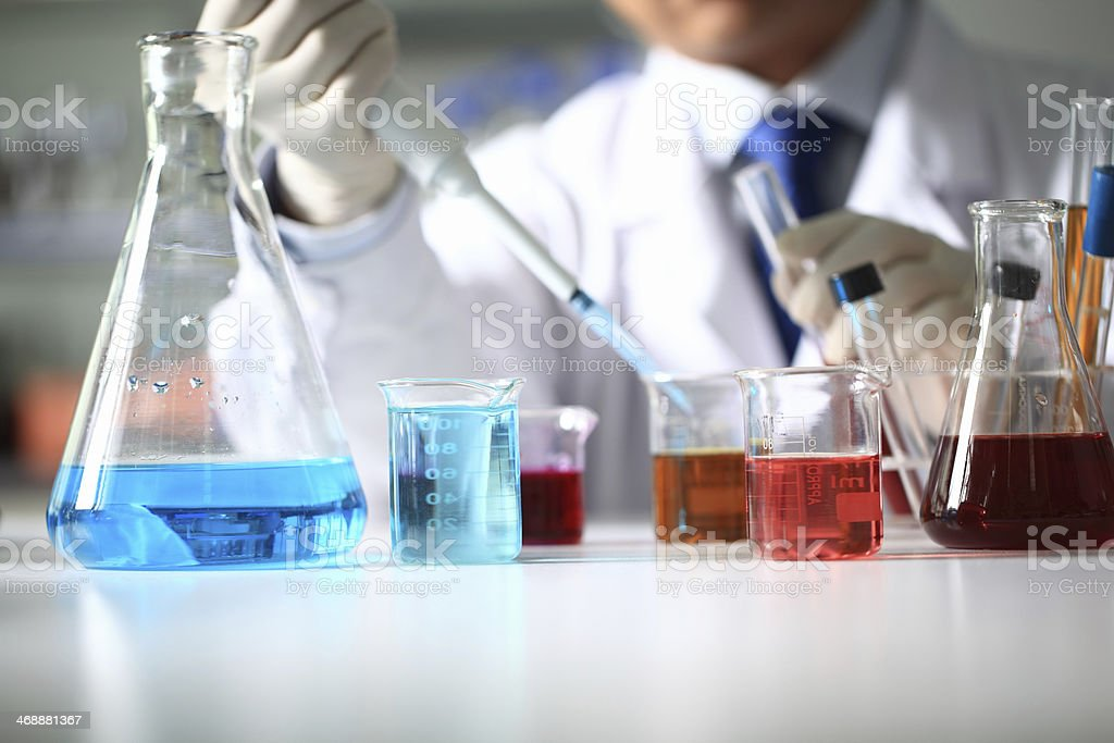 Scientist in lab coat using large pipette with flasks stock photo